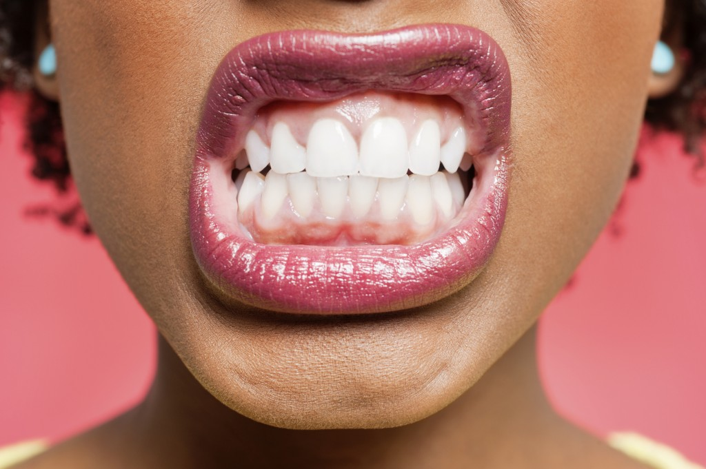 Cropped image of woman clenching teeth