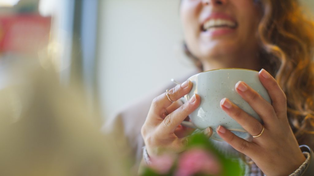 image of a woman holding a cup whilst talking
