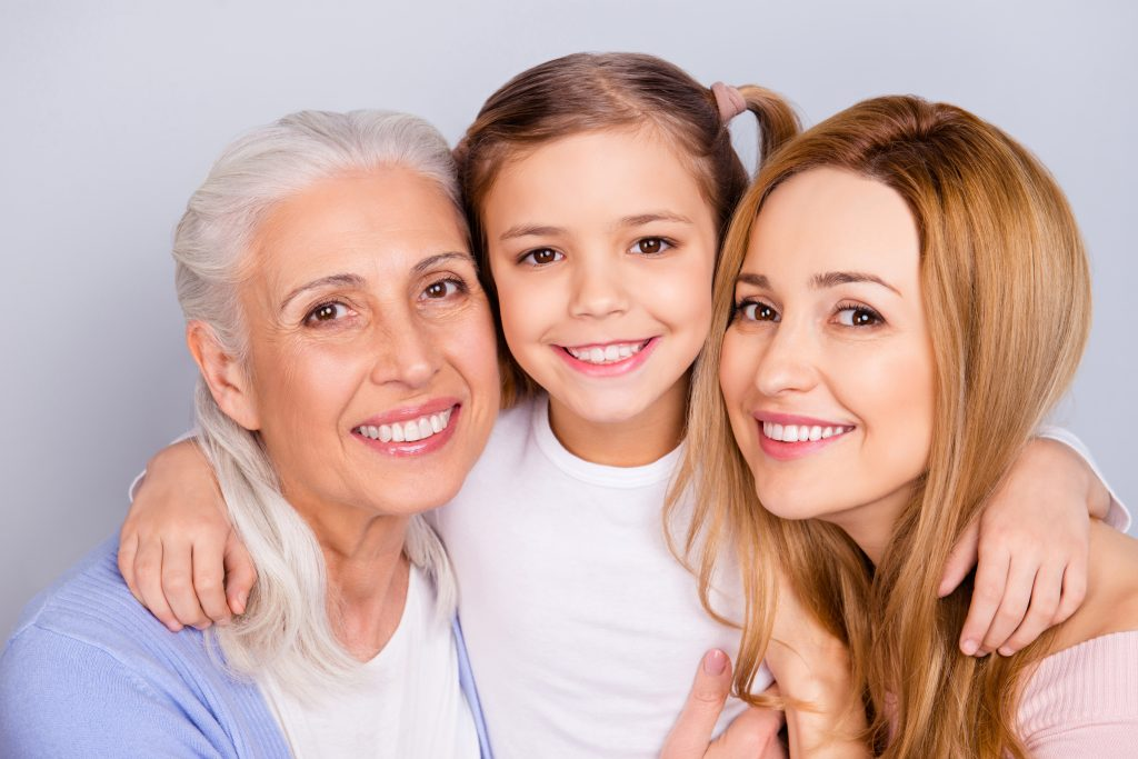 A grandmother, daughter and granddaughter smiling