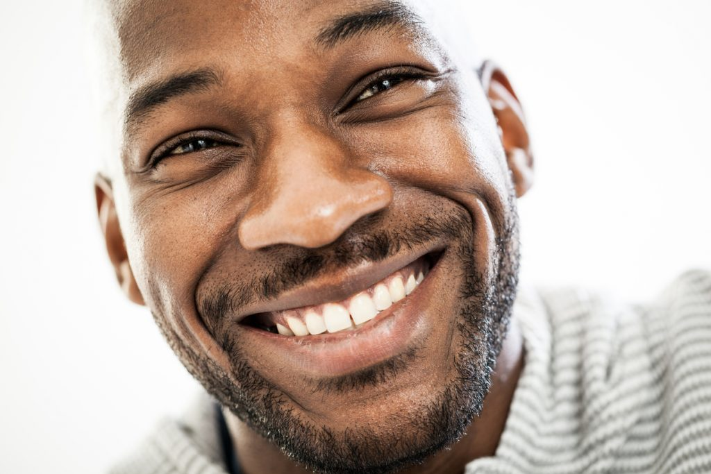 a close up view of a man with a smiling face and bright white teeth