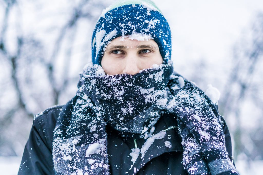 close up of a man's face with scarf covered by snow on a winter day