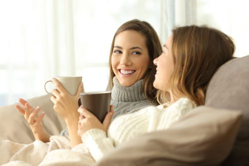 two women smiling and drinking hot drinks on a sofa