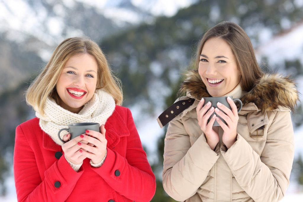Two smiling women drinking hot drinks outside in the snow