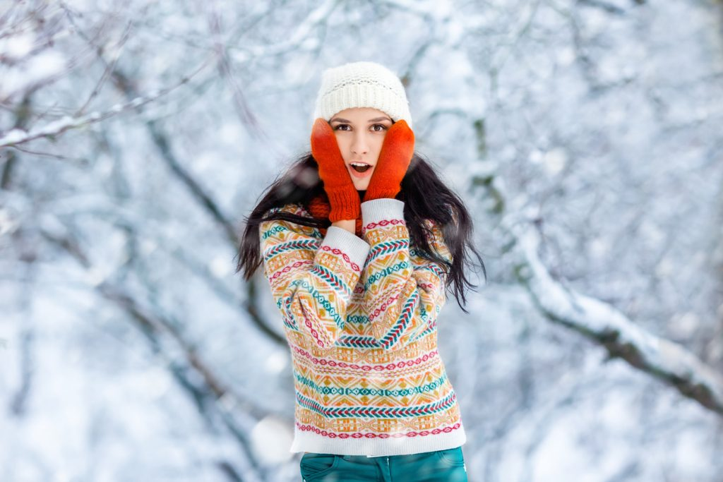 Young woman standing outside in the snow in front of a forest with red gloves on, touching her face with both hands