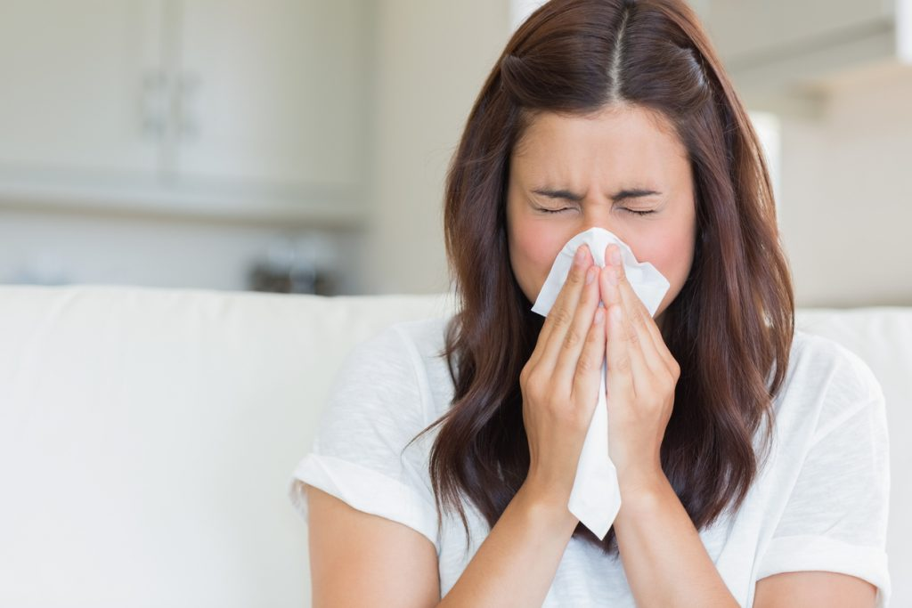 Brunette woman sneezing in a tissue in the living room
