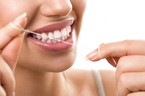 A woman cleaning her teeth with dental floss