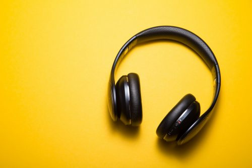 a pair of black wireless headphones on a yellow background