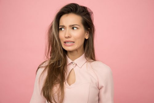 a young woman wearing a pink blouse looking scared