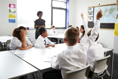British students putting their hands up in the classroom