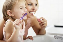 mother and daughter brushing teeth together in front of a mirror