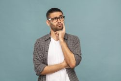 a man with glasses posing as if he is thinking