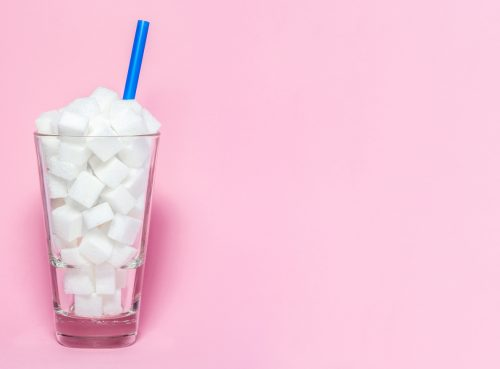 A glass full of sugar cubes with a blue straw and a pink background