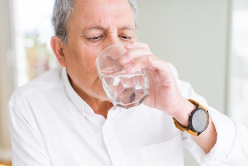 a senior man drinking a glass of water